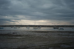 Fishing boats and small boats at low tide in UK on cloudy day Stock Photography