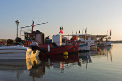 Fishing boats in a small fishing harbour at sunrise in Chalkidiki Stock Images