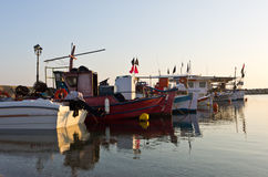 Fishing boats in a small fishing harbour at sunrise Stock Photo