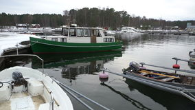 Fishing boats, snow and lead-gray water of the Baltic Sea. Dolly shot. stock video footage