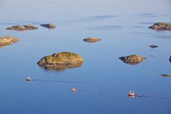 Fishing boats and tiny islands. Three fishing boats sailing out to the open sea near Henningsvaer, Norway Royalty Free Stock Image