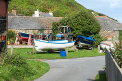 Fishing boats. With tractor in a backyard somewhere in Port Gaverne in Cornwall. Picture taken from a public street Stock Image