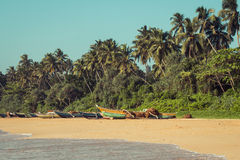 Fishing boats on a tropical beach with palm trees in the backgro Royalty Free Stock Image