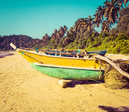 Fishing boats on a tropical beach with palm trees in the backgro. Fishing boats on a tropical beach with palm trees and mangrove in the background Royalty Free Stock Photos