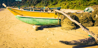 Fishing boats on a tropical beach with palm trees in the backgro Royalty Free Stock Images