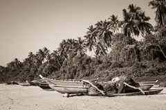 Fishing boats on a tropical beach with palm trees in the backgro Royalty Free Stock Photos