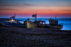 Fishing boats waiting to be launched from Hastings beach before dawn. Royalty Free Stock Images