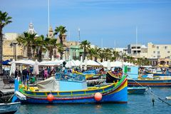 Fishing boats and waterfront restaurants, Marsaxlokk. Traditional Maltese fishing boats and Dghajsa boats in the harbour with waterfront buildings to the rear Stock Photo