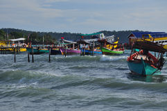 Fishing boats and waves, Koh Rong island, Cambodia. Koh Rong island, Cambodia.  traditional coloured wooden fishing boats. Main beach tropical holiday village Stock Photography
