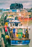 Fishing boats in Whitstable harbour, Kent, UK. At low tide small fishing industry boats can be seen in the harbour with nets and baskets Royalty Free Stock Photo