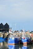 Fishing Boats in Whitstable Harbour in portrait view with warehouse in background Stock Image