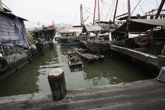Fishing boats are at the wooden pier in the port of Macau. Stock Photos