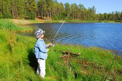 Fishing Boy 12. Boy at edge of lake watching fishing pole Stock Photos