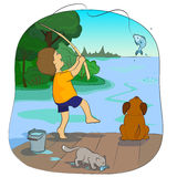 Fishing. Boy with a dog fish on the lake Royalty Free Stock Photography