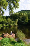 Boy fishing by river. Young child sitting by the river on a wood log with an fishing rod. River Lot, Cantal/Aveyron, France. Portrait orientation Royalty Free Stock Image