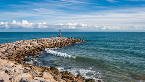 Fishing in the breakwater. Sea views next the beach and the breakwater Stock Photography