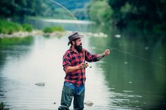 Fishing. Brutal man stand in river water. Man bearded fisher. Man fishing on the lake. Hobby for soul. Just do that only