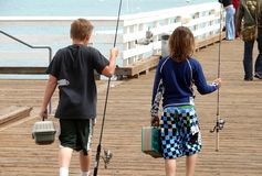 Fishing Buddies. Two friends head out to fish off a pier Stock Photos