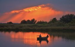 Fishing on a calm evening. Two fishermen in a boat fishing as the sun sets Royalty Free Stock Photography