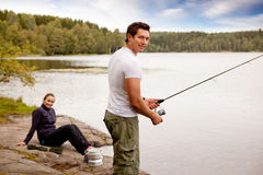 Fishing on Camping Trip. A man fishing on a lake with camping equipment and woman in background stock photography