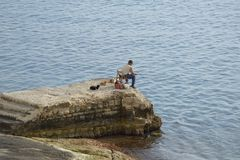 Fishing with cats in Malta. Fisherman surrounded  by cats in Malta Stock Photo