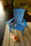 Fishing Chair On Deck. A wooden blue chair sitting on the dock with a fishing rod resting on it and a generic open tackle box in front.  Water naturally blurred Stock Photography