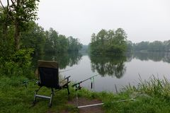 Fishing. Chair and  rods on the shore of a lake Royalty Free Stock Photo