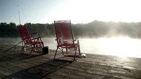 Fishing chairs standing at fishing pier on background morning fog over water. Morning fishing on pier on background fog over river. Chairs and fishing rods on stock footage