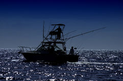 Fishing charter. Silhouette fishing charter out in the Atlantic ocean with outriggers against dark blue skies Royalty Free Stock Image