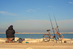 Fishing. CHIOGGIA, ITALY - JANUARY, 01: Fisher man with fishing rods and bike on January 01, 2016 Stock Photo