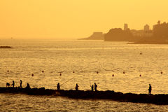 Fishing on the Coast. People fishing on a pier with the sea in the background in the late afternoon in Spain during summer Royalty Free Stock Image