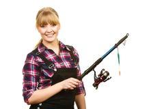 Similing woman wearing check shirt holding fishing rod royalty free stock images