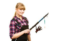 Similing woman wearing check shirt holding fishing rod. Fishing concept. Attractive woman in dungarees, pink check shirt holding rod. Isolated background Stock Images