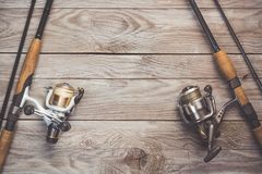 Fishing concept. Fishing spinning rods and reels with lines on wooden background with free space.  stock photo