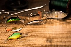 Fishing concept with gear, artificial bait on a predator on a wooden background, top view wobblers and various bait royalty free stock photo