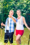 Fishing couple, man and woman, on lake being proud of catch stock photo