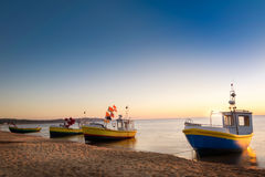 Fishing cutters on the shore. Sun just rises over colorful fishing cutters on sandy beach. Baltic sea, Pomerania. Poland royalty free stock image