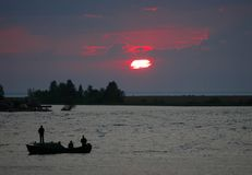 Fishing on a decline. / Decline of summer evening. Fishermen by a boat fish in twilight stock image