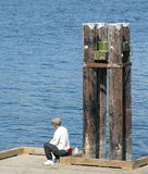 Fishing on the Dock. A man sitting on a dock and fishing in the Pacific Ocean Stock Photos