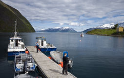 Fishing from dock in fjord. A man fishing from a long boat dock on a scenic fjord in Norway Stock Photo