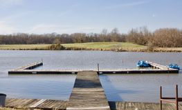 Fishing Dock at a Lake. A fishing dock that extends out into a river for fishing and paddle boat rides stock photography