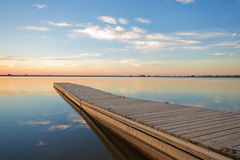 Fishing dock on a lake at sunrise with soft wispy clouds Royalty Free Stock Photography