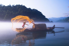 Fishing on the Dongjiang Lake. Fishing-boat on the Dongjiang Lake surrounded by mist flowing along the mountains and on the surface. The lake is located in Stock Photography