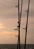 Fishing at Dusk. Silhouette of fishing poles at ocean at dusk Royalty Free Stock Photography