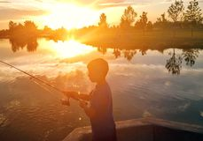 Fishing at dusk. Evening. Light sun boy fishing Stock Images