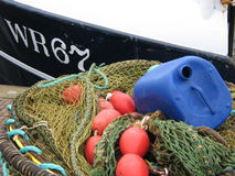 Fishing nets. Boat with fishing nets and floatline in harbour Stock Photos