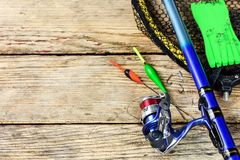 Fishing equipment on a old wooden table. Fishing tackle. Fishing rod, floats, fishing hooks and landing net on old wooden background with free space for text stock photo