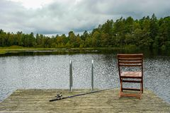 Fishing equipment on seat on lake. Feeder carp rods on wooden pier royalty free stock image