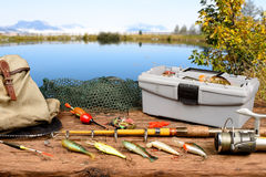 Fishing equipment. On a wooden table with lake in background Royalty Free Stock Photography