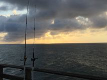 Fishing, Faith and Fulfillment. Dusk approaches as a peaceful day of fishing an Atlantic Ocean pier Stock Image